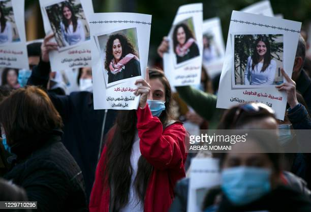 Palestinian women lift placards during a rally in support of 41 women detained in Israeli prisons in the city center of Ramallah in the occupied West...