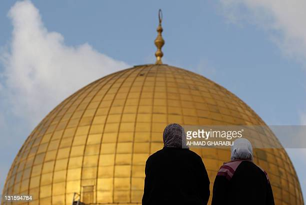 Palestinian women look at the golden roof of the Dome of Rock inside the AlAqsa Mosque compound Islam's third holiest site following the morning Eid...