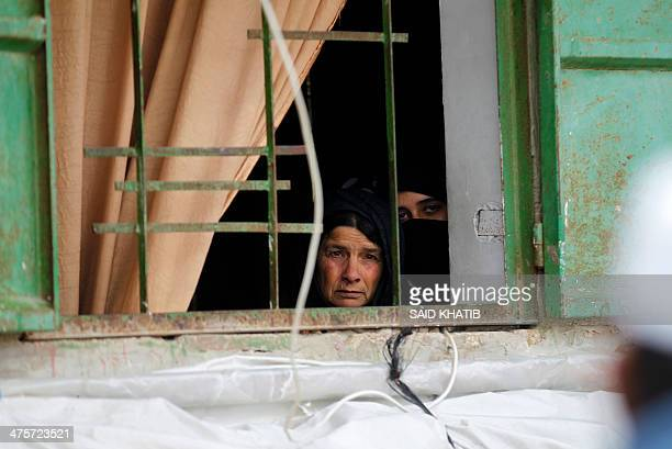 Palestinian women look out from a window as mourners carry body of Amena Atiyyeh Qdeih a mentally ill Gazan woman who was shot dead by Israeli troops...