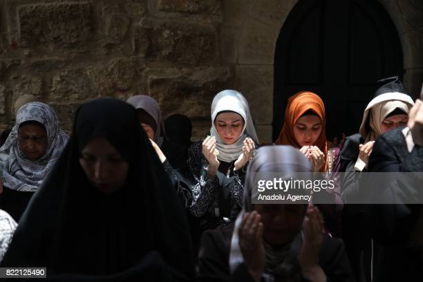 Palestinian women perform a prayer in front of Al-Aqsa Mosque Compound to stage a demonstration after Israeli authorities decided to remove metal...