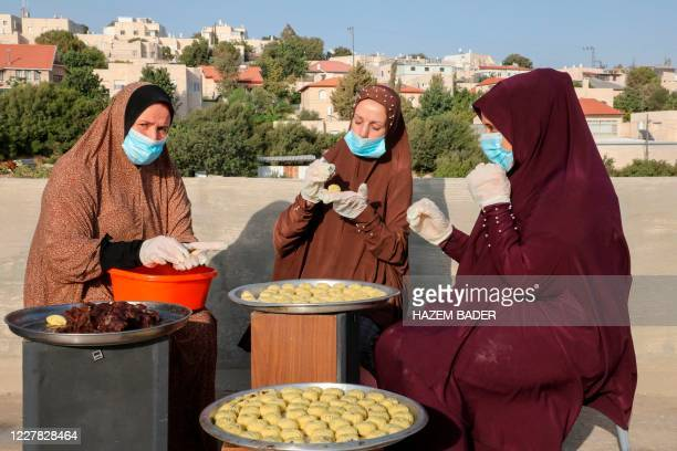 Palestinian women prepare traditional datefilled cookies on the roof of their house in the West Bank city of Hebron on July 29 2020 in preparation...