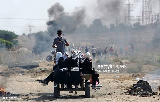Palestinian women protesters sit in the back of a cart during clashes with Israeli security forces near the Nahal Oz border crossing with Israel east...