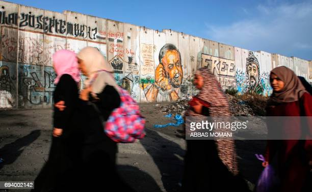 TOPSHOT Palestinian women queue up past a mural of Fatah leader Marwan Barghuti painted on a section of Israel's controversial separation wall next...