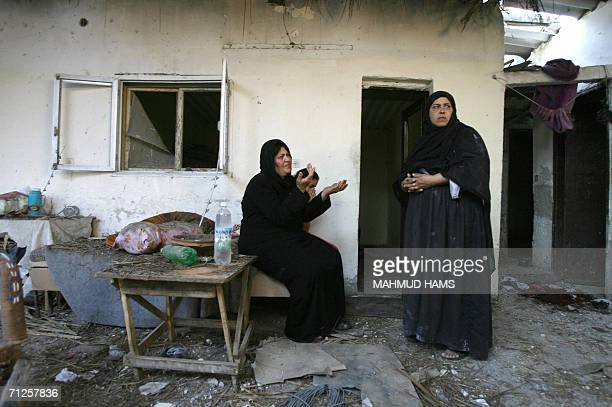 Palestinian women sit in the grounds of a damaged residence close to where a woman was killed after the house was hit during an Israeli missile...