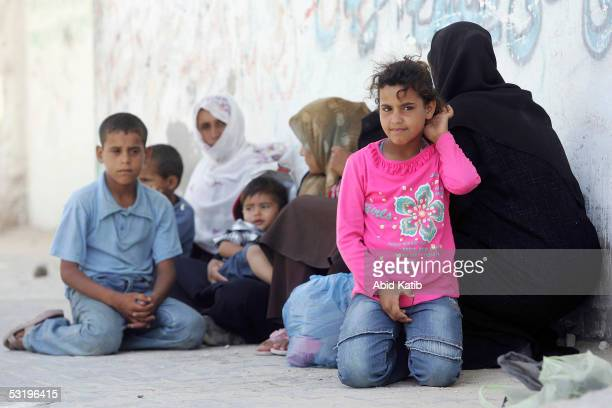 Palestinian women sit with their children in the street near the Israeli settlement of Nefeh Dakalem after the Israeli troops closed the checkpoint...