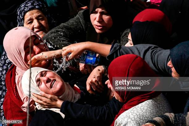 TOPSHOT Palestinian women sprinke water from a bottle to comfort the mother of 17yearold Palestinian Ayman Hamed who was fatally shot by Israeli...