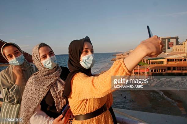 Palestinian women takes a selfie at sunset in Gaza city amid strict restrictions due to the COVID-19 pandemic on October 12, 2020.