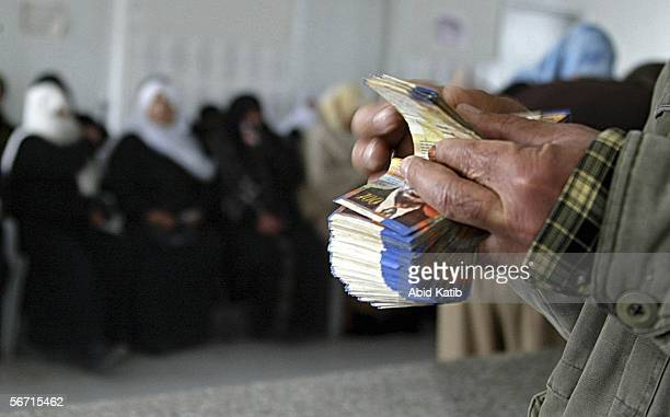Palestinian women wait to receive aid money for their needy relatives at the Islamic AlSalah Charitable Society on February 1 2006 in Gaza City Gaza...
