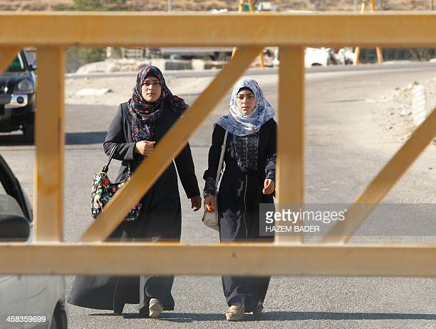 Palestinian women walk past a barrier blocking the road at the southern main entrance of Hebron on July 2 after Israeli troops locked down the...