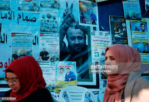 Palestinian women walk past a wall bearing posters including a portrait of Palestinian leader and prominent prisoner Marwan Barghouti during a rally...