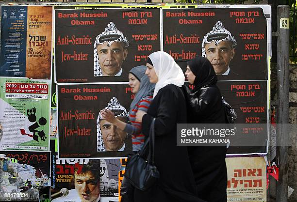 Palestinian women walk past antiUS President Barack Obama posters in Jerusalem on June 14 2009 The posters which depict Obama wearing a traditional...