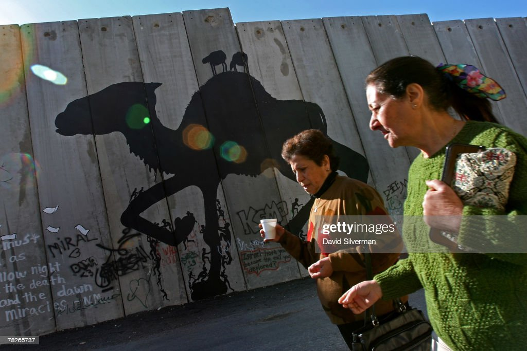 Palestinian women walk to work past graffiti of a camel, attributed to a Spanish artist called Sam3, on Israel's separation barrier December 5, 2007 on the outskirts of the biblical West Bank city of Bethlehem. Dozens of large-scale artworks by various artists, along with some by elusive British artist Banksy, are part of an exhibition called Santa's Ghetto.