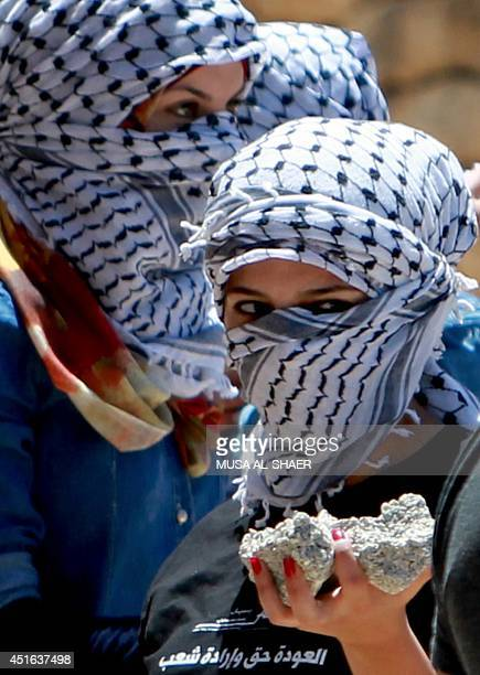 Palestinian women wearing a traditional Keffiyeh head scarf gather stones to be thrown at an Israeli guard tower in the West bank city of Bethlehem...