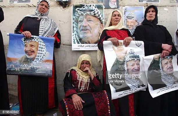 Palestinian women weep next to poster of the late Palestinian leader Yasser Arafat near the Muqata, Ramallah compound on Nov. 11, 2004. Arafat was...