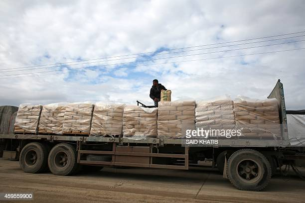 A Palestinian worker adjusts bags of cement loaded on a truck that entered the Gaza Strip from Israel through the Kerem Shalom crossing in Rafah in...