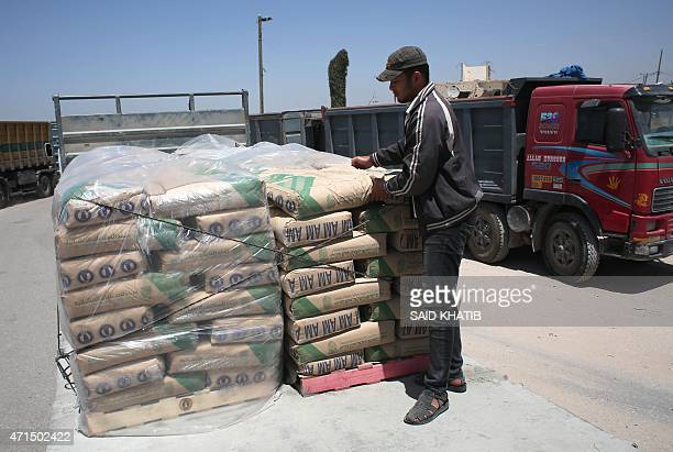 A Palestinian worker adjusts bags of cement loaded on the back of a truck after it entered the southern Gaza Strip from Israel through the Kerem...