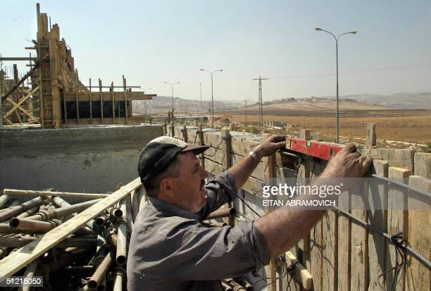 Palestinian worker builds new houses in the West Bank settlement of Adam 24 August 2004 The grand dream of the 600 residents of Adam of becoming a...
