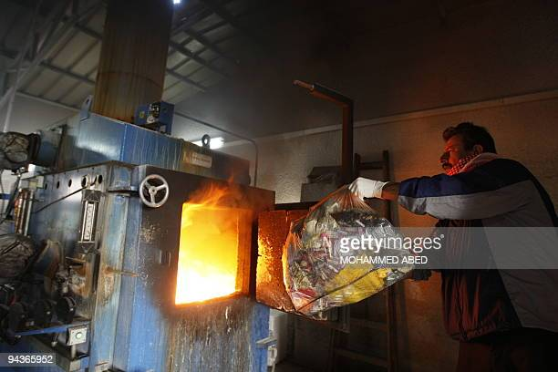 Palestinian worker burns waste in AlShifa hospital's incinerator in Gaza City on December 13 2009 The incinerator whose operation does not meet the...