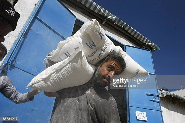 A Palestinian worker carries bags of flour at a UN Relief and Works Agency food distribution center in the Gaza City Shati refugee camp on November...