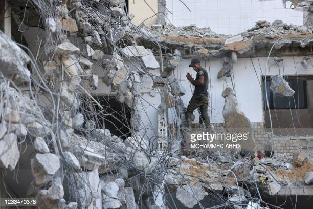 Palestinian worker inspects a building destroyed by Israeli air strikes last month in Gaza City on June 15, 2021. - With tensions high amid a fragile...