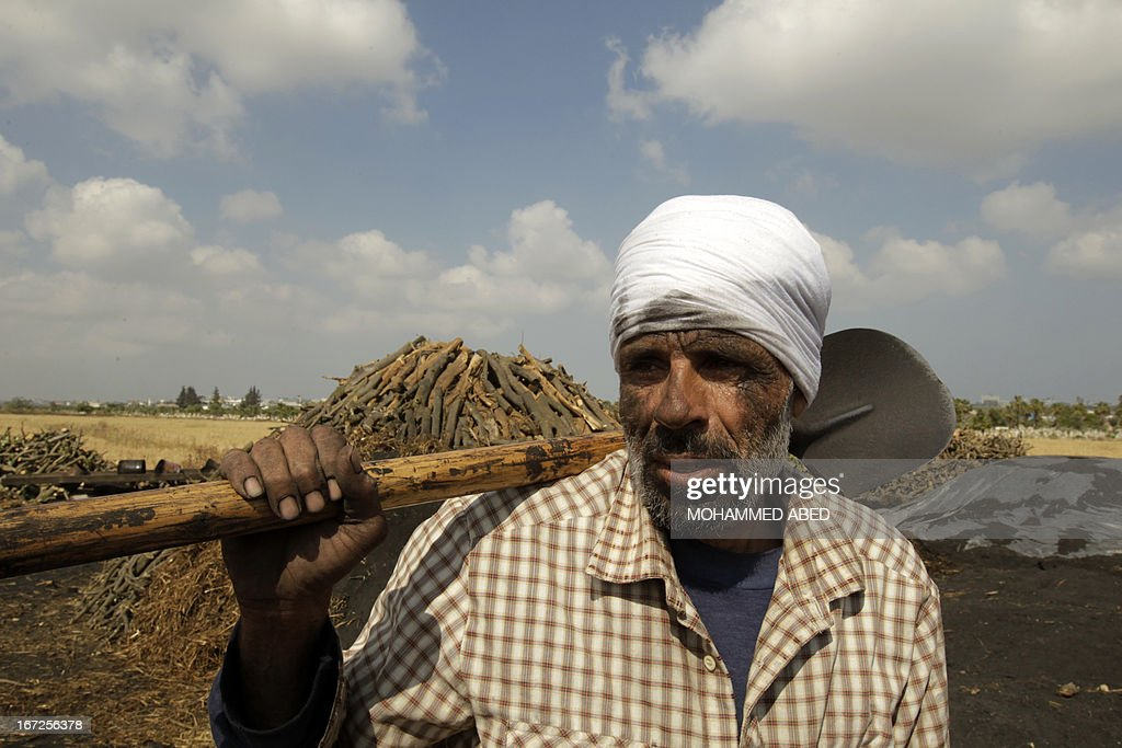 A Palestinian worker is seen with his spade as he collects coal at one of the few local charcoal manufacturing plants east of Gaza City on April 23, 2013.