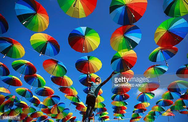 Palestinian worker of a beachside coffeehouse decorates its terrace with hanging colourful umbrellas as part of decorations for the Muslim holy...