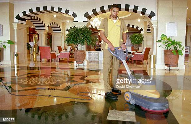 Palestinian worker polishes the floors of the otherwise deserted lobby of the recentlyopened Intercontinental Hotel and Oasis casino October 29 2000...
