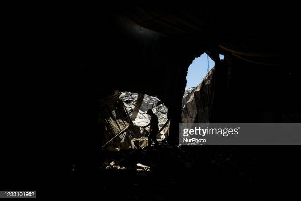 Palestinian worker salvages items from a damaged factory in Gaza's industrial area, on May 25 which was hit by Israeli strikes prior to a cease-fire...