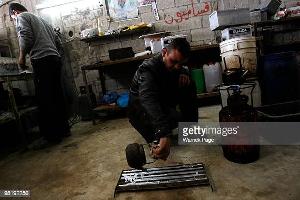 Palestinian worker, Shaher al-Helou pours melted recycled-metal into a mould at a car-battery workshop March 29, 2010 in Jabaliya, Gaza Strip....