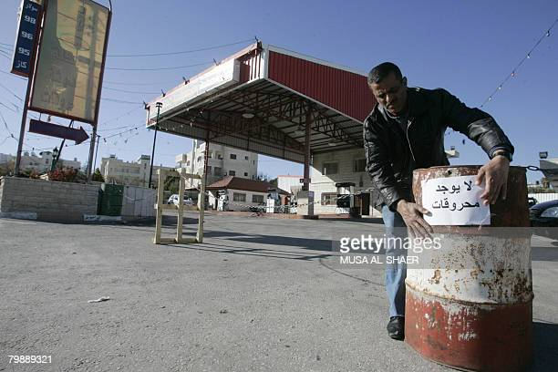 A Palestinian worker sticks a sign reading 'no fuel' outside a gas station in the West Bank town of Bethlehem on February 21 2008 Gas station owners...