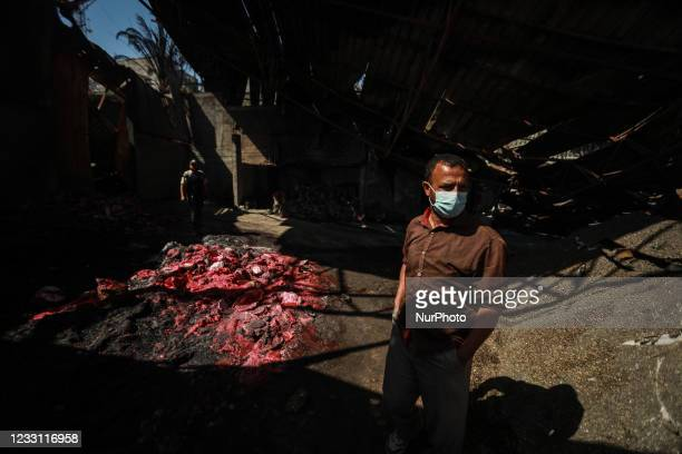 Palestinian worker tries to recover items from a damaged agricultural fertilisers factory destroyed in recent Israeli air strikes, in Beit Lahia, on...