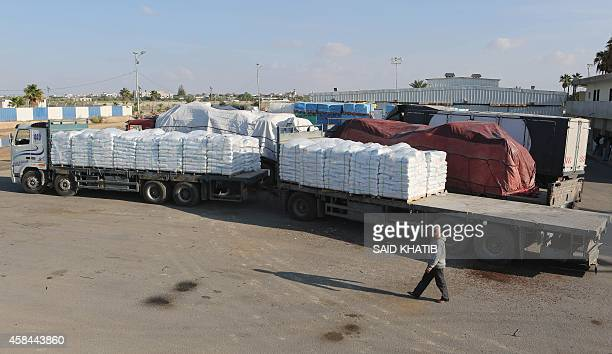 A Palestinian worker walks pasat bags of cement loaded on a truck that entered the Gaza Strip from Israel through the Kerem Shalom crossing in Rafah...