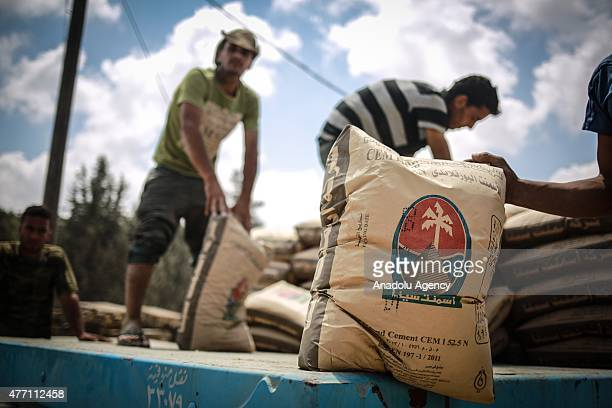 Palestinian workers adjust bags of cement loaded on a truck that entered the Rafah from Egypt on June 14 after Egyptian authorities reopened the...