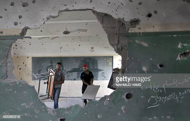 Palestinian workers are seen through a damaged wall as they carry tables in a classroom at a goverment school in Gaza City on September 13 2014 one...