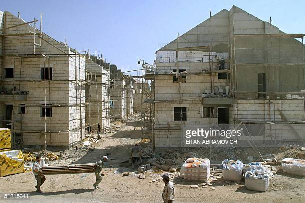 Palestinian workers build new houses in the West Bank settlement of Adam 24 August 2004 The grand dream of the 600 residents of Adam of becoming a...