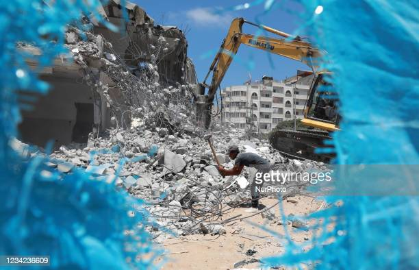 Palestinian workers clear the rubble of buildings, leveled by Israeli bombing during the conflict between Israel and Hamas in May this year, in Gaza...