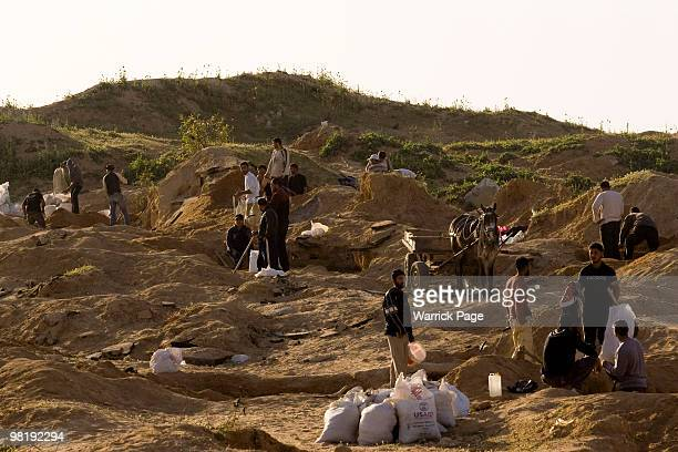 Palestinian workers dig for stone close to the Israeli border March 22, 2010 in Beit Lahiya, Gaza Strip. In the last few months the demand for stone...