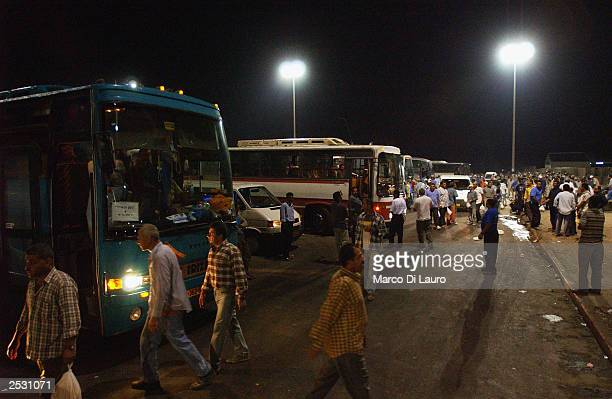 Palestinian workers get on buses after crossing into Israel from the Gaza Strip on September 24 2003 at the Erez border crossing point IsraelThe...