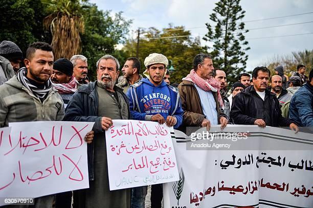 Palestinian workers hold banners and shout slogans as they march toward United Nations Coordination Office during a protest against Israeli blockade...