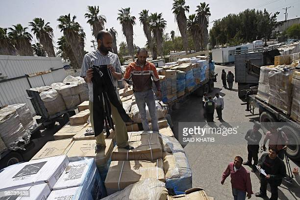 Palestinian workers inspect trucks carrying clothes and shoes upon their arrival in Rafah through the Kerem Shalom crossing between Israel and the...