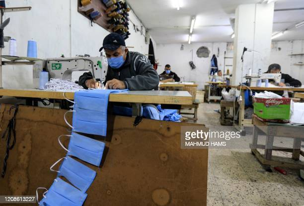 Palestinian workers manufacture protective coverall suits and maks at a workshop in Gaza City on March 30 2020 amid coronavirus COVID19 pandemic The...