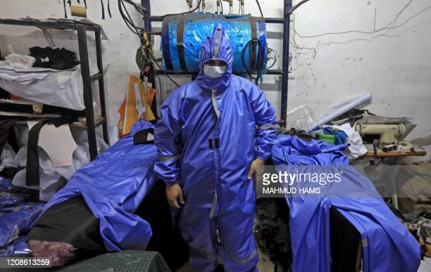 Palestinian workers manufacture protective coverall suits and maks at a workshop in Gaza City on March 30, 2020 amid coronavirus COVID-19 pandemic. -...