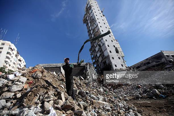 Palestinian workers participate in efforts to clear the rubble of a Building that witnesses said was destroyed by Israeli shelling during the most...