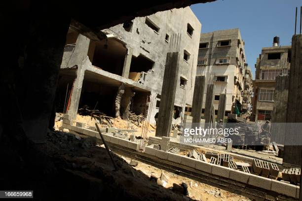 Palestinian workers rebuild a house in Gaza City in which Mohammed al-Dallu, a Hamas policeman described by the Israeli army as a terrorist, was...