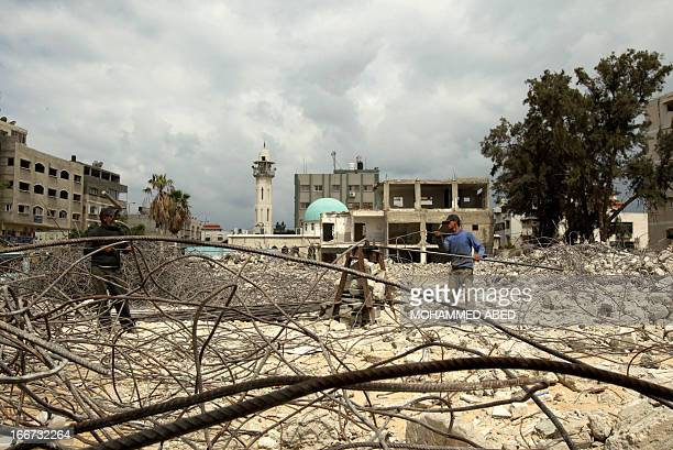 Palestinian workers remove rubble from the ruins of a Hamas security forces headquarters that was destroyed during Israel's last November Gaza...