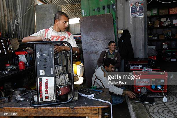 Palestinian workers repair broken generators at the market on March 28 2010 in Rafah Gaza Strip Power cuts in Gaza are growing more and more frequent...
