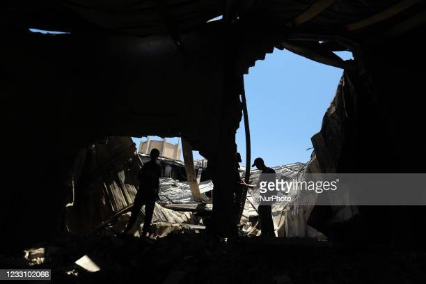 Palestinian workers salvage items from a damaged factory in Gaza's industrial area, on May 25 which was hit by Israeli strikes prior to a cease-fire...