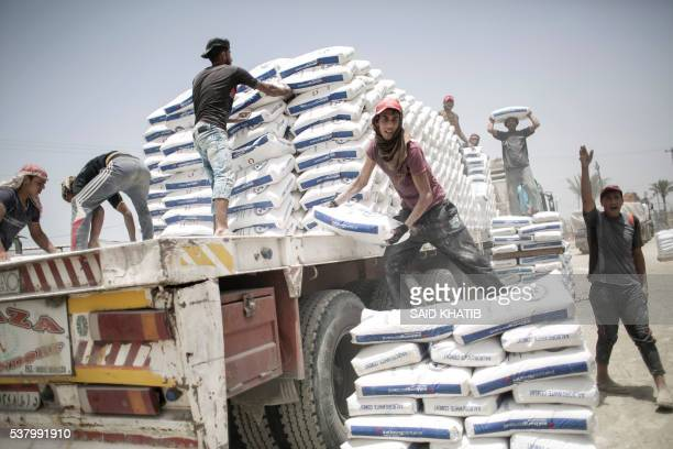 TOPSHOT Palestinian workers unload bags of cement from a truck after it entered the southern Gaza Strip from Egypt through the Rafah border crossing...