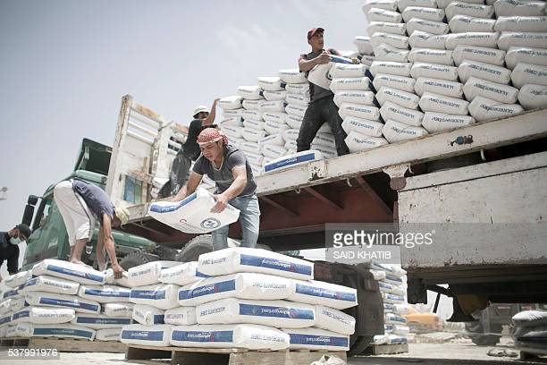 Palestinian workers unload bags of cement from a truck after it entered the southern Gaza Strip from Egypt through the Rafah border crossing on June...