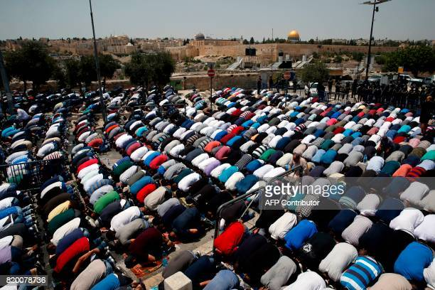 Palestinian worshippers pray outside Jerusalem's Old City in front of the AlAqsa mosque compound after Israeli police barred men under 50 from...